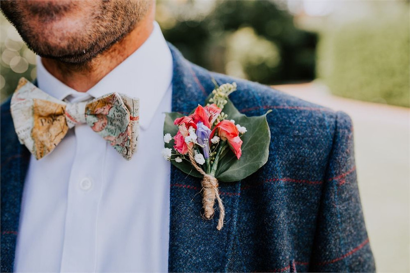 Man's chest in a suit with bow-tie and floral buttonhole