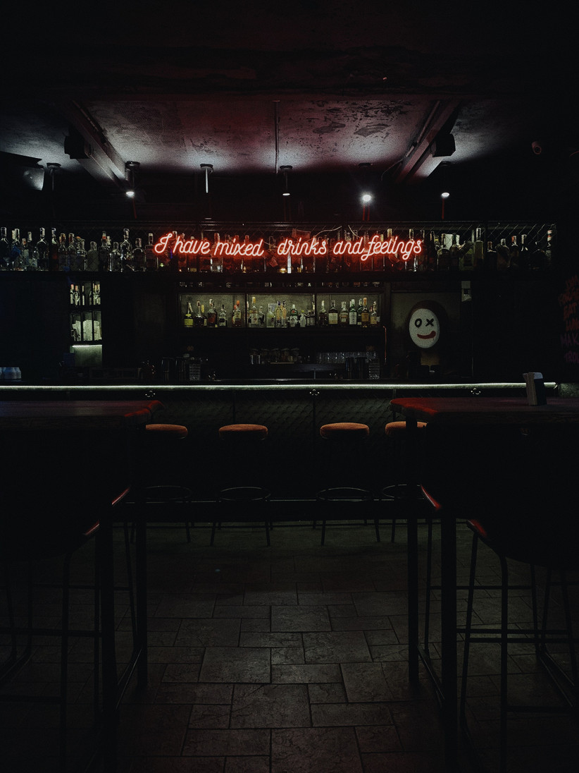 Empty bar with a neon sign that reads I have mixed drinks and feelings