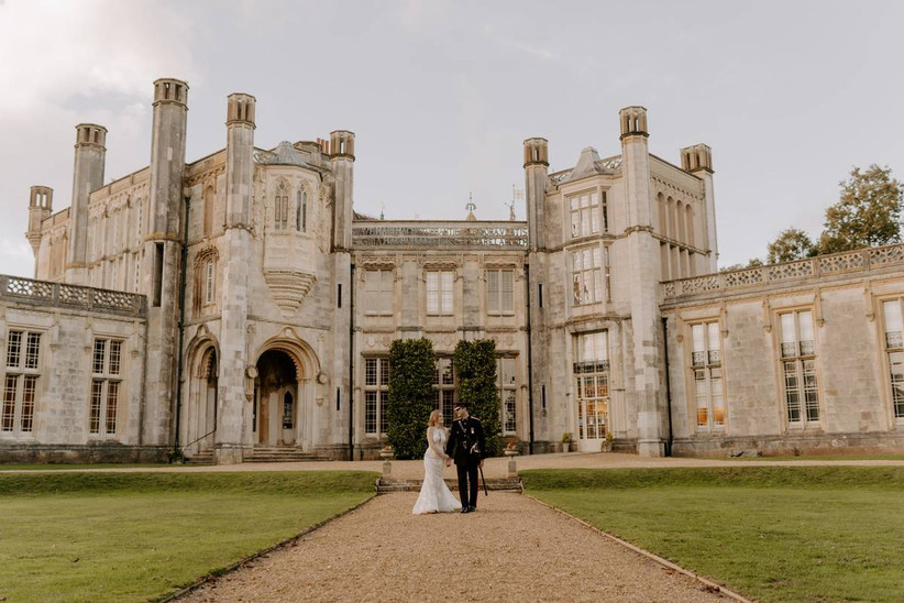 Bride and groom stand outside a grand castle