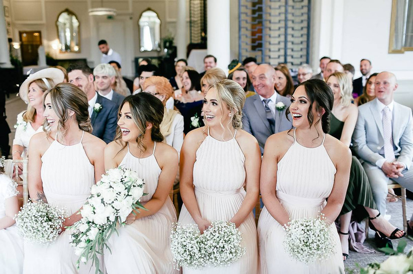 Wedding guests smile at a ceremony