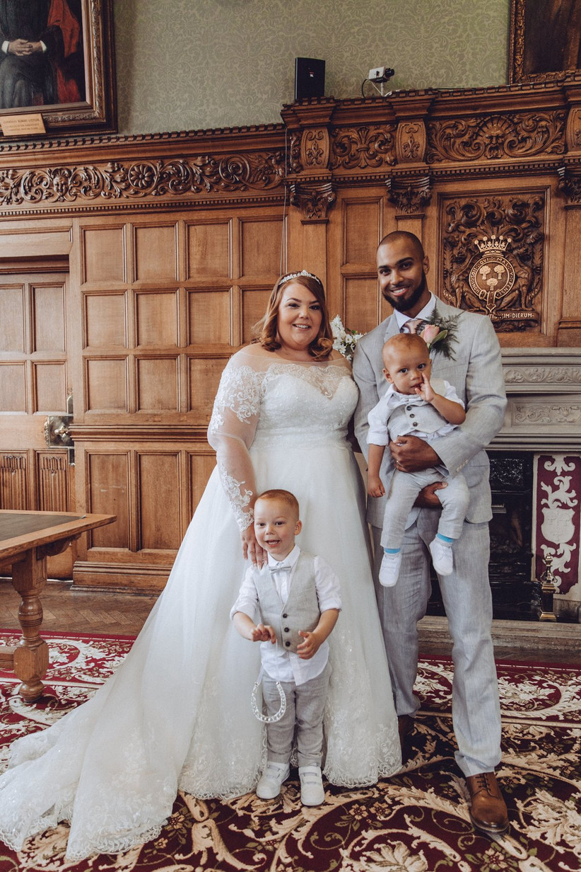 Plus size bride and groom posing indoors for a wedding photo with two children