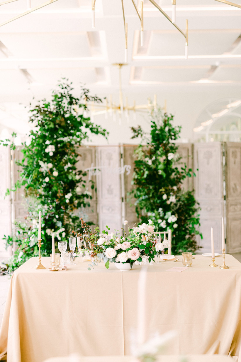A wedding reception with pink flowers on the tables, candles in gold holders and an opulent flower and foliage arch