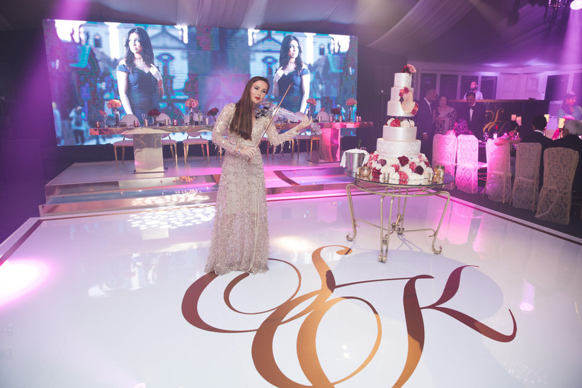 Woman playing a violin on a dance floor next to a multiple-tiered white wedding cake