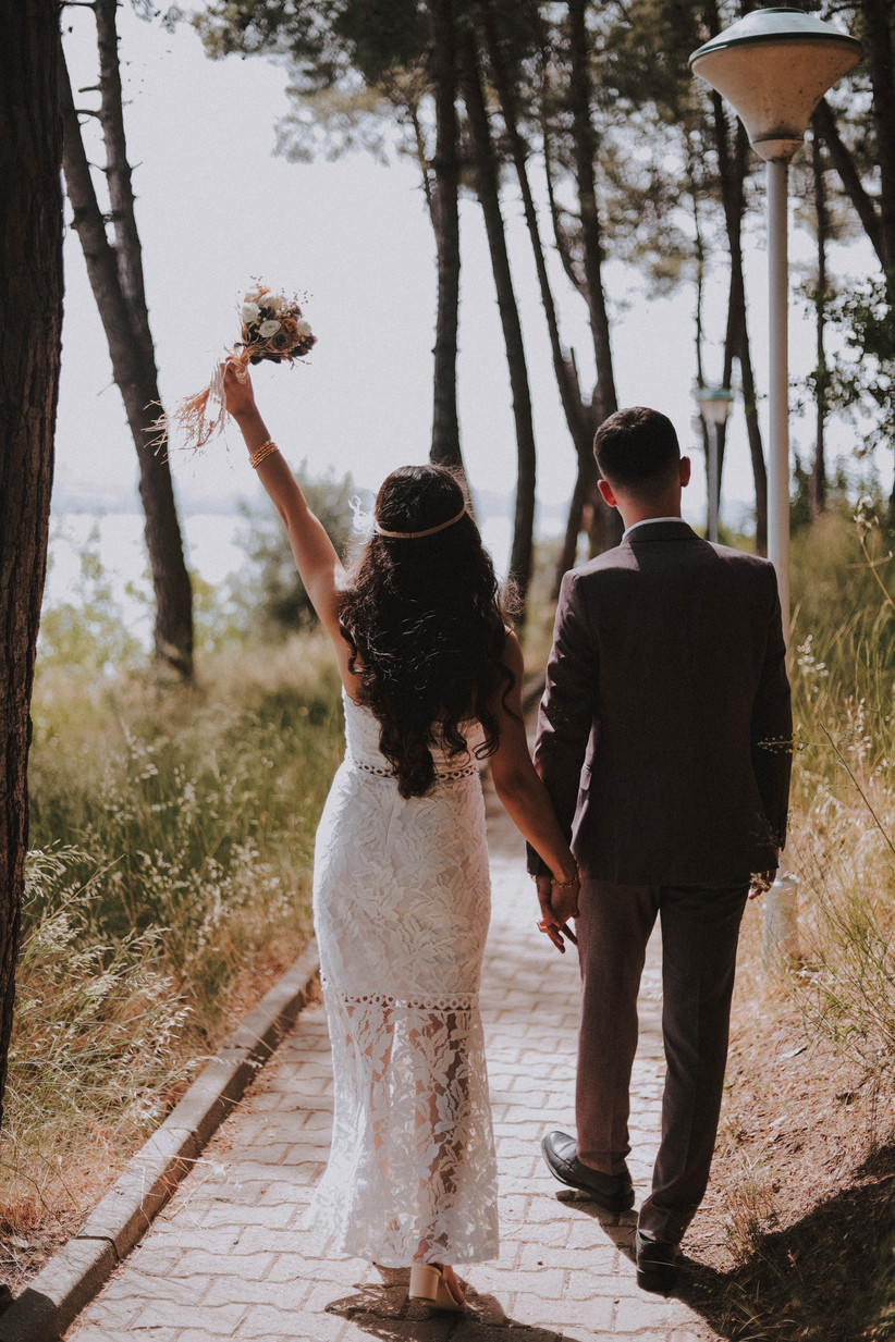 Bride and groom walking along a pathway in the sun