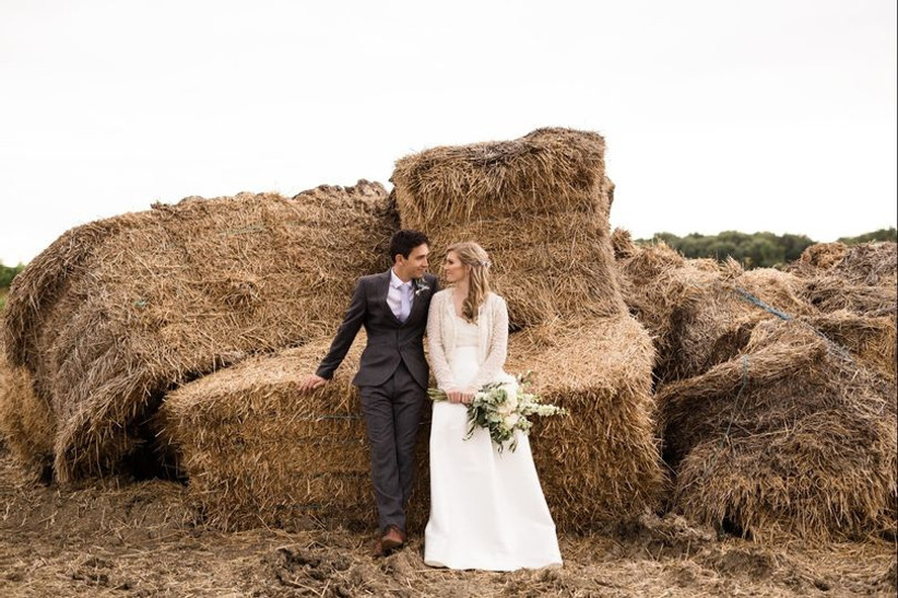 Bride and groom sit together on haybales