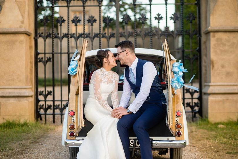 Bride and groom seated on the wedding car - Laura Ellen Photography