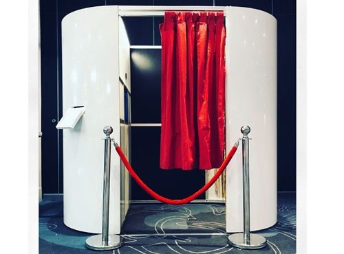 Enclosed DJ booth with red curtain and rope
