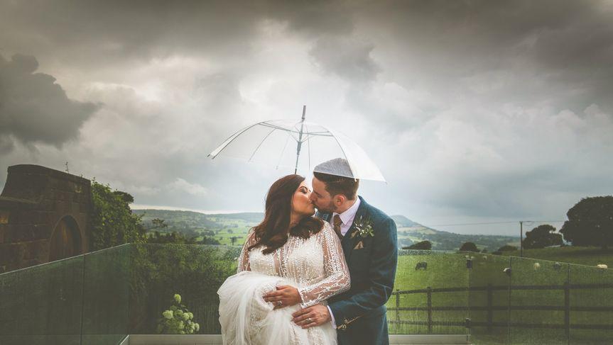 Couple standing under an umbrella - Jon Thorne Weddings