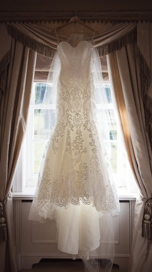Wedding dress hangs in sunlit window