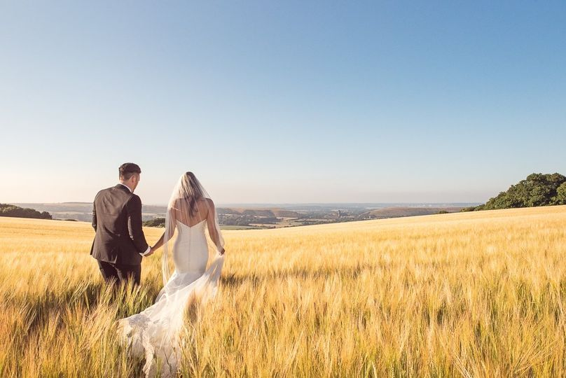 Newlyweds walk across field on the Isle of Purbeck