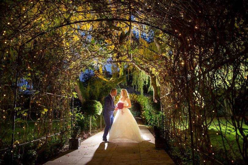 Newlyweds under greenery arch
