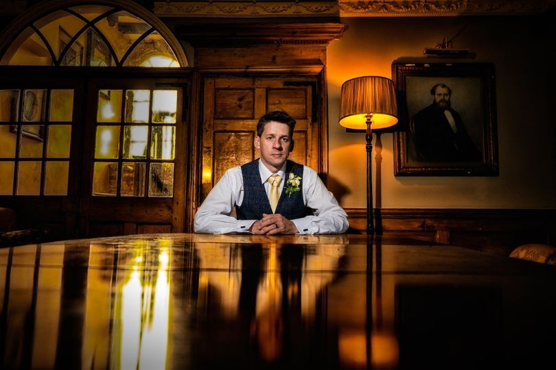 Groom seated at a table - Creating Diamonds Wedding Photography