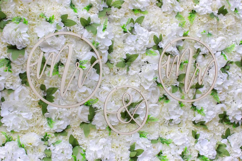 Floral backdrop with wedding signs