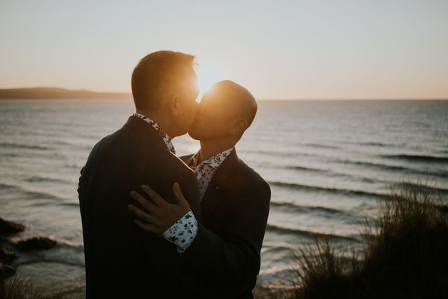 Grooms kissing at Sunset