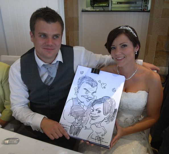 Bride and groom get their caricature done at the end of the speeches during a wedding breakfast in...