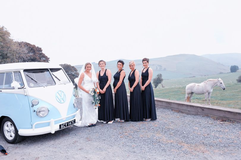 Bride and bridesmaids beside a classic van