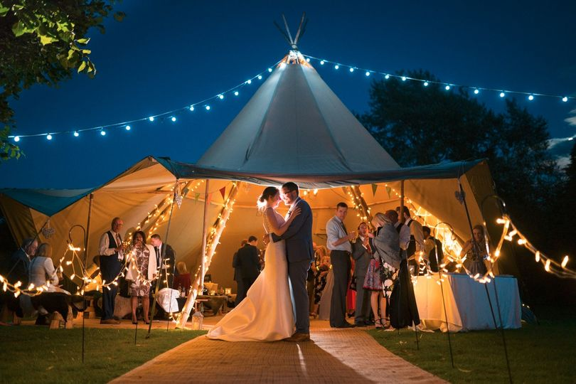 Bride and Groom by a night-time tipi