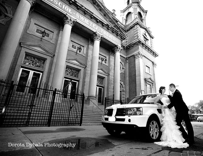 bride and groom standing by range rover by holy trinity catholic church chicago1 4 108408