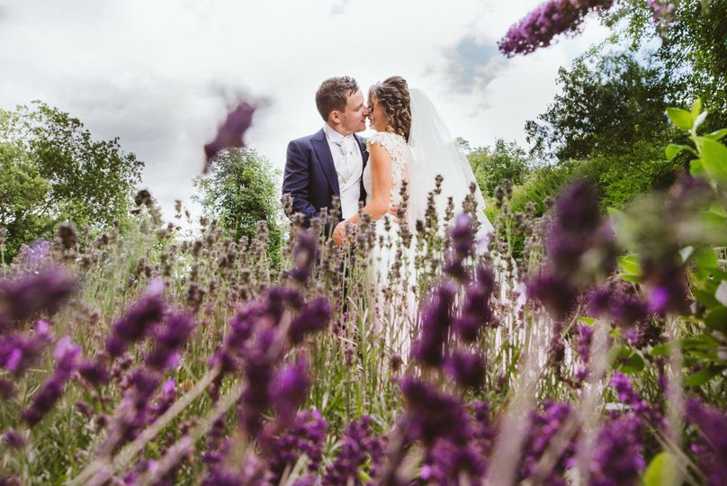 Newlyweds in a field of purple flowers