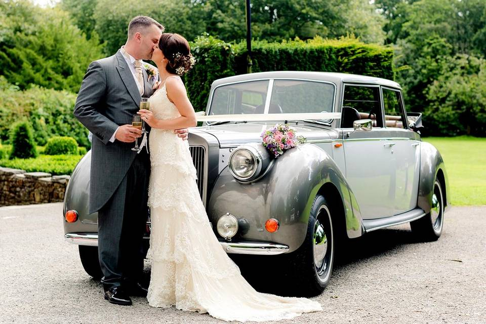 Newlyweds standing in front of a classic car