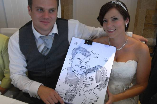 Bride and groom get their caricature done at the end of the speeches during a wedding breakfast in The Bay Hotel in Newquay